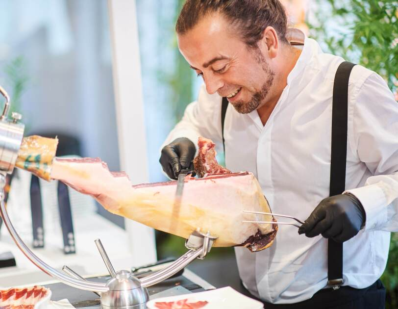 Redondo Iglesias specialized in traditional Spanish Ibérico and Serrano ham at Amazon Academy open marketplace exhibition, slicing ham for the visitors.