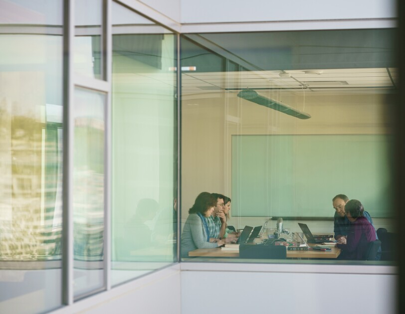 In an image made from another part of the building and photographed through a window, three women and two men sit at a conference table.