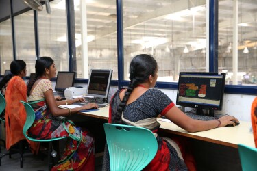 Women in traditional apparel working at desktop computers