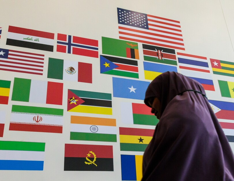 A woman walks past a wall decorated with a large American flag and smaller flags from nations around the world.