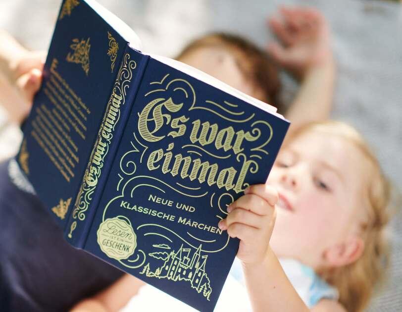 Zwei Kinder lesen zusammen in einem Märchenbuch