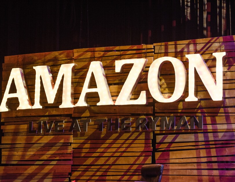 "Amazon ""Live at the Ryman"" stage sign from Nashville event. The sign is three panels wide, each panel made up of pieces of horizontal wood that are fit together. There are lighted letters that spell ""Amazon,"" with ""Live at the Ryman"" below."