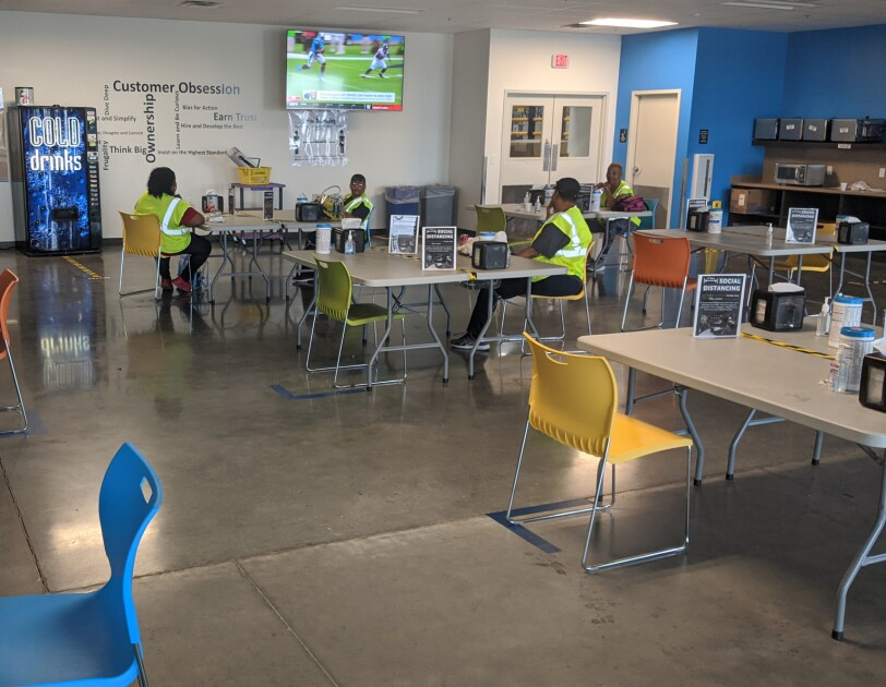 Workers in safety vests sit at separate tables in a break room where the tables have been spaced to support social distancing measures.