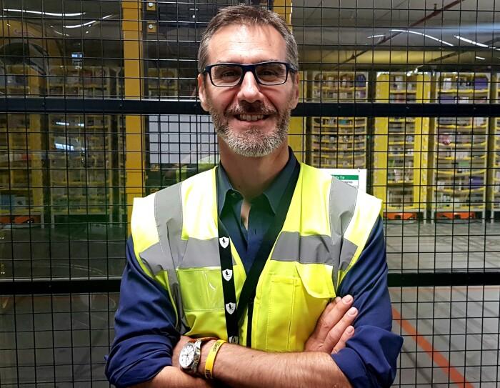 Salvatore Iorio, Country HR Manager di Amazon Italia Logistica, sorride a mezzo busto con le braccia conserte all'interno di un'area di un magazzino Amazon. Indossa degli occhiali da vista, un giubbino catarinfrangente giallo e una camicia blu.