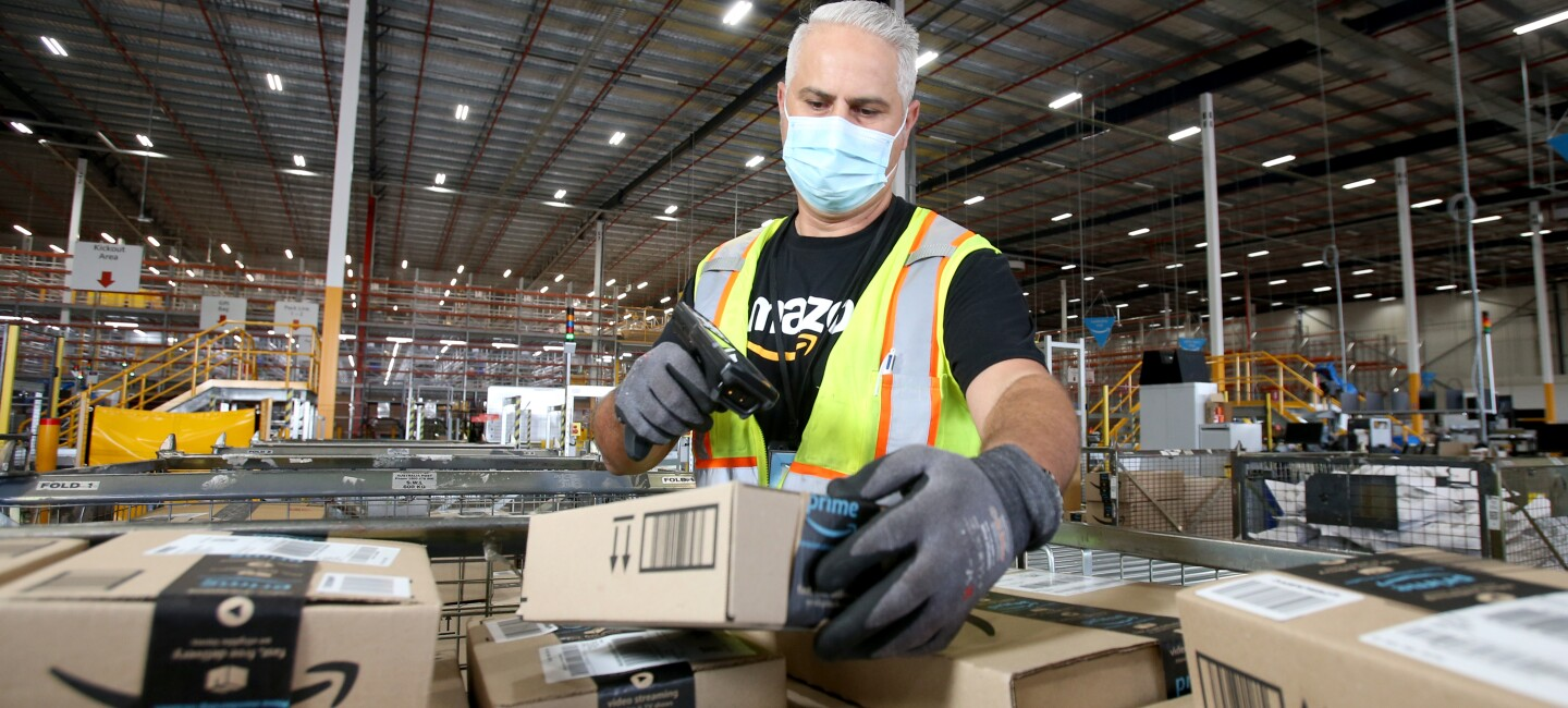 Fil works at  Amazon's Brisbane fulfilment centre, scanning parcels about to be shipped to customers