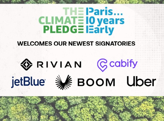 Fotografía de un bosque t delante en un cuadro blanco The Climate Pledge, Paris 10 years early welcomes our newest signatories y los logos de Rivian, Cabify, jetBlue, Boom y Uber.