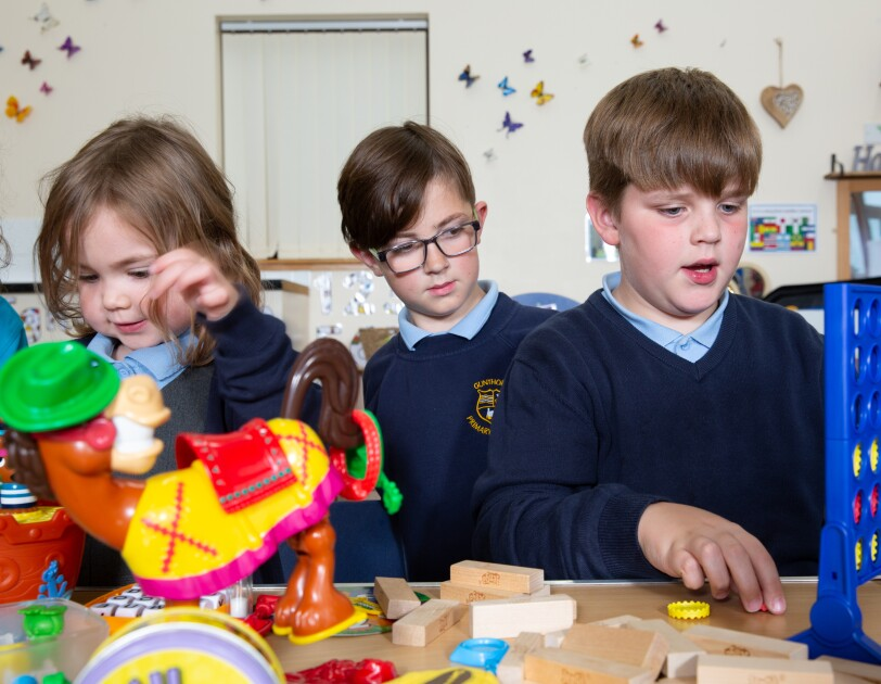 Three school children playing various games on a table, there is Connect Four, Buckaroo, Jenga and others.