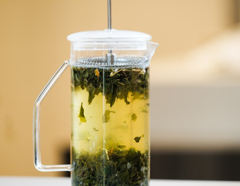 Tea leaves float in hot water in a press-style teapot.
