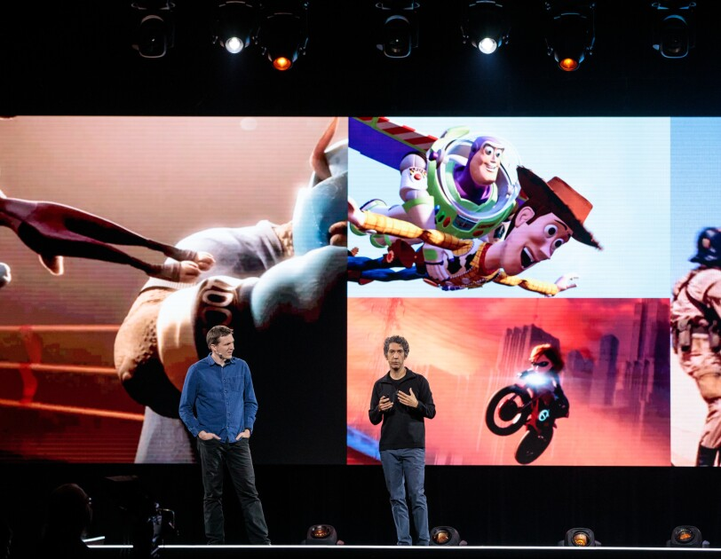 Two men, Morgan Pope and Tony Dohi stand on stage at Amazon re:MARS, in front of a screen showing Disney characters in motion.