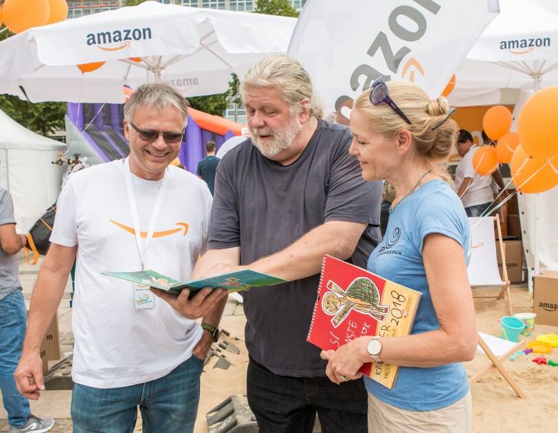 Rulo Lange ist in der Bildmitte zu sehen. Links Standortleiter Dietmar Jüngling, rechts eine Dame. Rulo Lange zeigt beiden ein KInderbuch. Im Hintergrund ist der SachsenBeach in Leipzig zu sehen, der von Amazon gesponsert wurde.
