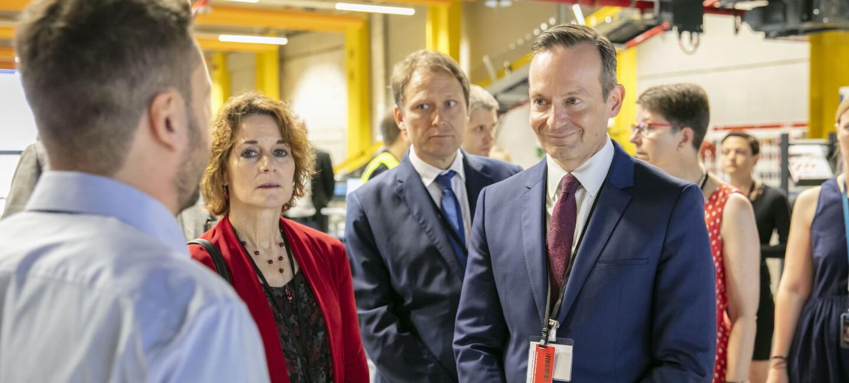 Standortleiter Johannes Weingärtner (im Rücken zu sehen) erklärt Oberbürgermeister Hebich und Landesminister Wissing die Abläufe. Im Hintergrund sieht man weitere Gäste sowie Teile der Logistikhalle.