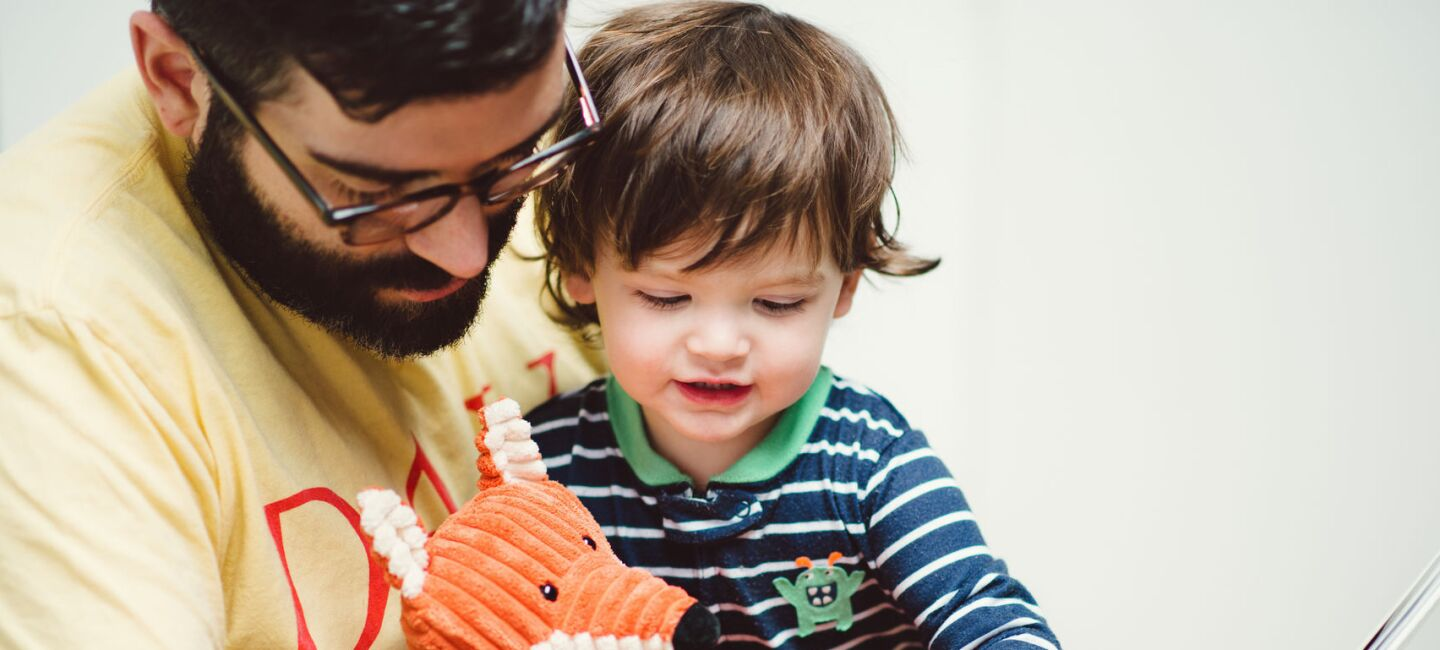 A man with a beard and glasses reads to his young son.