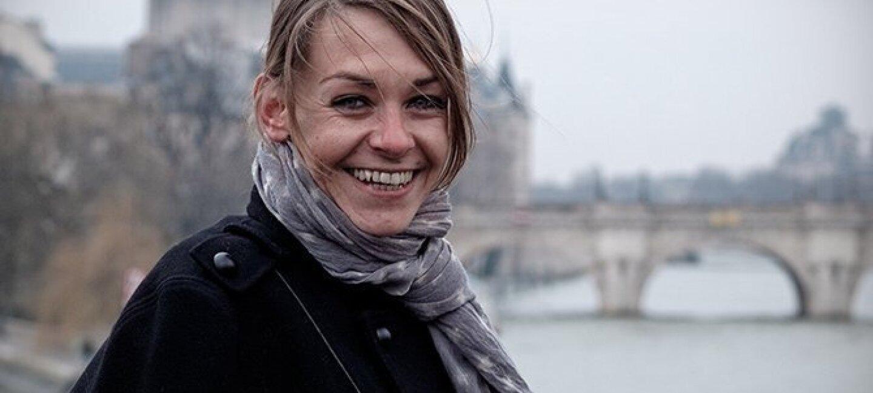Portrait en buste d'Agnès Martin-Lugand en extérieur devant un pont surplombant une rivière à côté d'un château