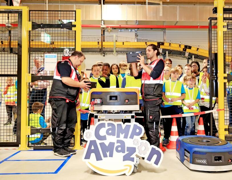 Eine Gruppe von Kindern hat sich in einer Logistikhalle rund um einen Transportroboter versammelt, der auf einem Tisch steht. Zwei Amazon Mitarbeiter erklären ihnen die Funktionsweise.