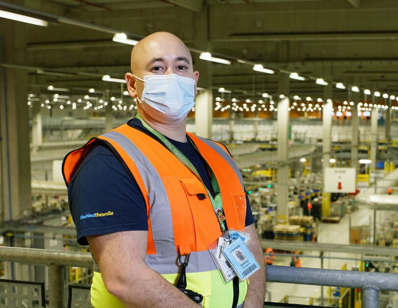 Antony Georgiou, Operations Apprentice at Amazon's fulfilment centre in Swansea, packing a customer order.