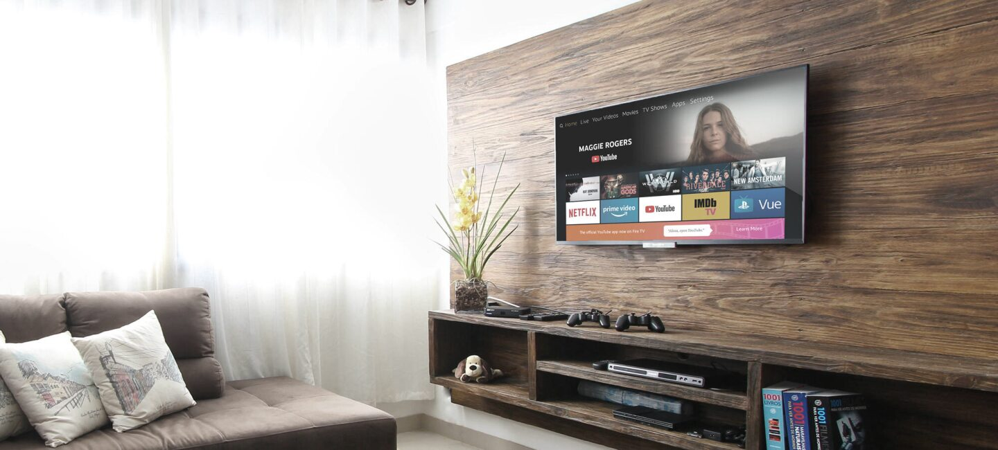 A television is displayed on a wall, showing the YouTube on FireTV experience. Below the television is a console with books, dvds, and a gaming system. A sectional sofa is also partially visible in the image.