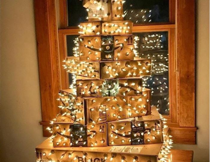 Adorno navideño de DQA2. Delante de una ventana de madera hay un árbol de Navidad hecho de cajas de Amazon y está envuelto de luces de decoración.