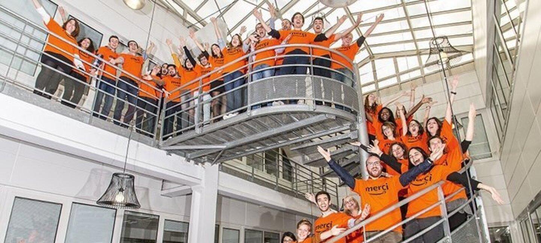 """Plusieurs dizaines d'employés d'Amazon Clichy se tiennent sur un escalier en colimaçon en fer, dans l'atrium du bureau. Ils portent un t-shirt orange où est écrit """"Merci"""" avec l'Amazon Smile et ils lèvent les bras en criant."""