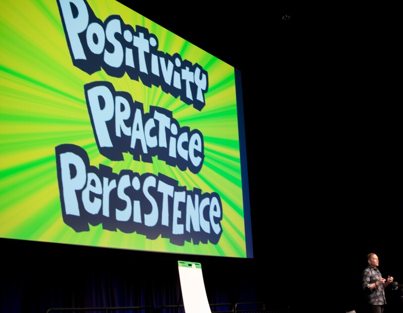"""A man on a stage stands in front of a large screen displaying the words """"POSITIVITY PRACTICE PERSISTENCE."""""""