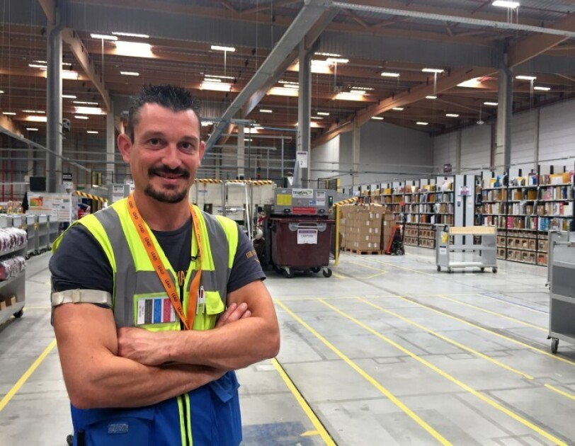 The image of Lionel Boulbes at the facilities center in his yellow vest with boxes and trays in the background. He is a French Amazon associate working at Montmelier facilities center in France.