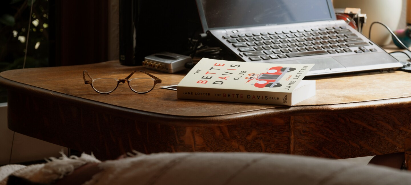 A copy of The Bette Davis Club on a home office desk. Behind the book is a laptop computer and a pair of glasses.