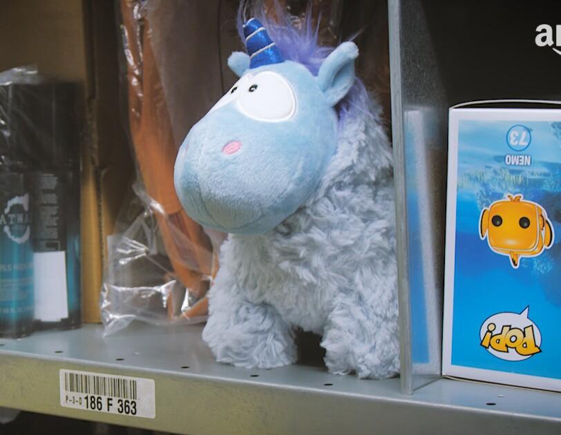 Ein blaues Plüsch-Einhorn steht in einem Lagerregal, zwischen diversen Artikeln.