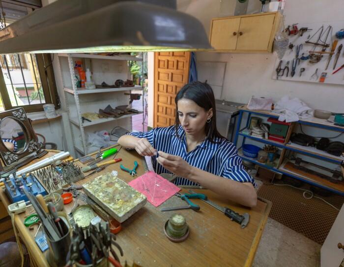 Sonia Llamas tiene 28 años y hace tres creó Iyé Biyé, su propio negocio online de joyería. Con el pelo largo castaño, lleva una camisa de rayas blancas y azules y se encuentra sentada en una mesa de su taller y manipulando un collar. La mesa está llena de herramientas de joyería y en el fondo también se ven muebles con herramientas incluso colgadas en la pared. En primerísimo primer plano, en la parte superior hay un foco para trabajar.
