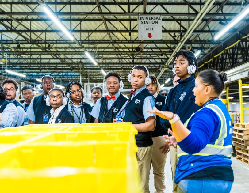 Students attend a tour of an Amazon robotics fulfillment center