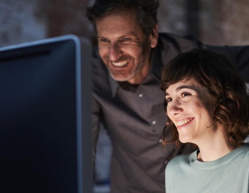 Mężczyzna i kobieta wpatrują się w monitor z uśmiechem