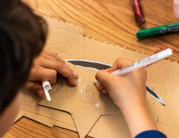 Diego, el hijo de marta y Fernando, dibujando una estrella para el árbol de Navidad. Primer plano de las manos de Diego. En la derecha un color blanco que ilustra la estrella. La estrella es de carta de cartón de Amazon. En la mano izquierda sujeta el tapón.