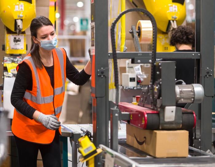 Una empleada de Amazon que se beneficia de una máquina de precintado automática. Una asociada con mascarilla quirúrgoca, camiseta negra de manga larga y pantalón negro. Lleva guantes, tiene el pelo blanco y está delante de una máquina de precintado automático.