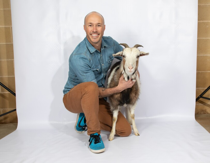 A man in a denim shirt and khaki pants with tennis shoes crouches on a white background. To his left is a small goat, with which he is posing. Both the man and goat are looking into the camera.