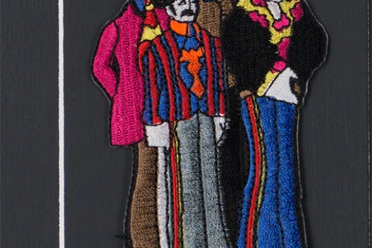 A sewn patch depicting the four members of the Beatles.