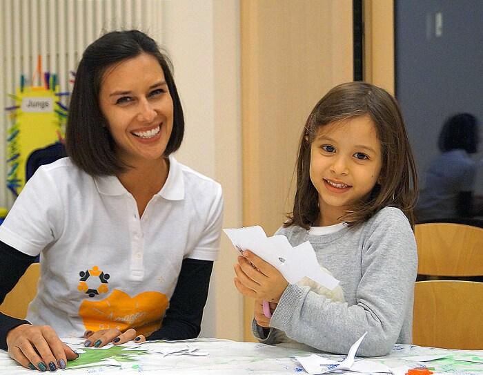 Eine junge Frau sitzt mit einem kleinen Mädchen an einem Tisch. Sie basteln gemeinsam.