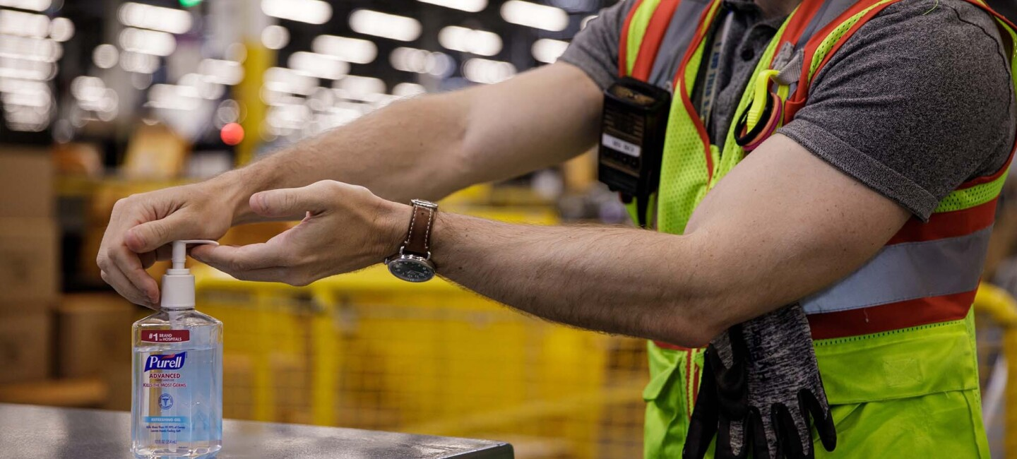 A man working in an Amazon fulfillment center pumps hand sanitizer into his palm.