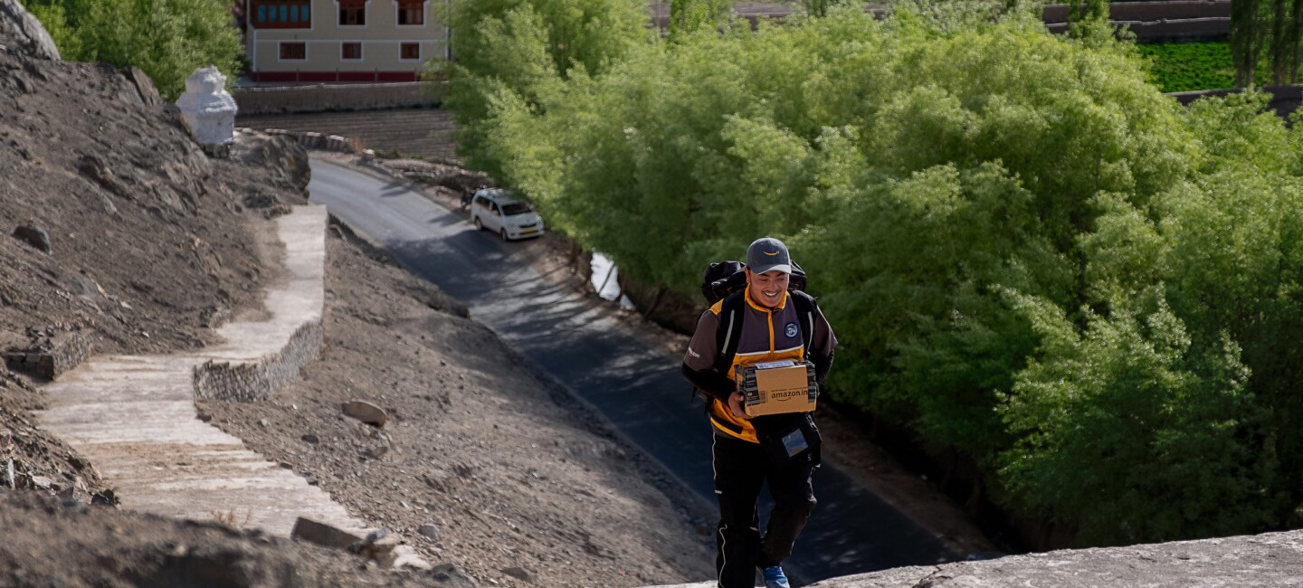 A smiling man in an Amazon delivery uniform carries a package up a staircase of at least 100 stairs that snakes along a hillside up from a road below. Trees and buildings are in the background of the image.