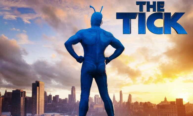 Promotional image for The Tick, showing the lead character standing on a high vantage point, looking out over a city skyline during a sunset.