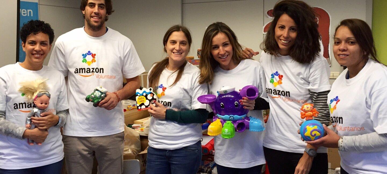 Seis voluntarios Amazon de las oficinas corporativas de Madrid muestran los juguetes solidarios que están preparando para donar durante la campaña de Navidad. Todos ellos visten con las camisetas blancas con el logo Amazon voluntarios. Hay cinco mujeres y un hombre.