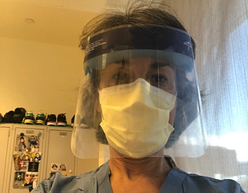 An image of Dr. Gore, a chidhood cancer researcher and physician, wearing a face mask and face shield in her scrubs.