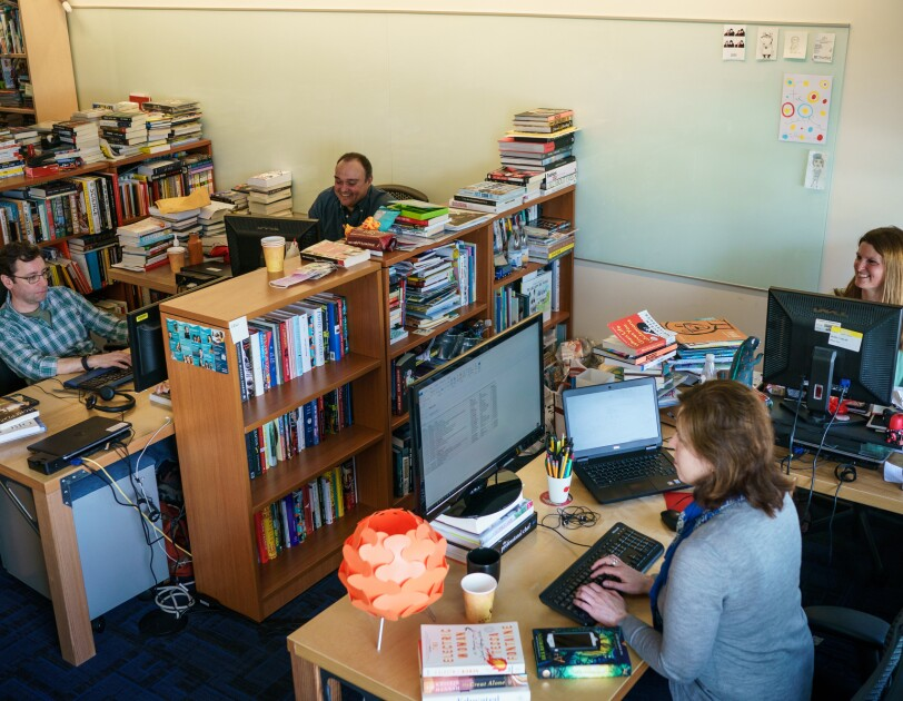 Two women and two men sit at desks and work at computers. They are in a shared office space with several full bookshelves, which also have small stacks of books on top of them.