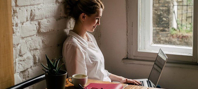En el salón de su casa, una mujer de mediana edad, está al lado de una ventana de madera, trabajando con el ordenador. Lleva una camisa blanca y el pelo recogido. En la mesa tiene una planta, una taza de café, las gafas, una agenda y el teléfono.