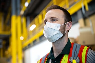 An associate in an Amazon fulfillment center with additional safety measures in response to the COVID-19 pandemic