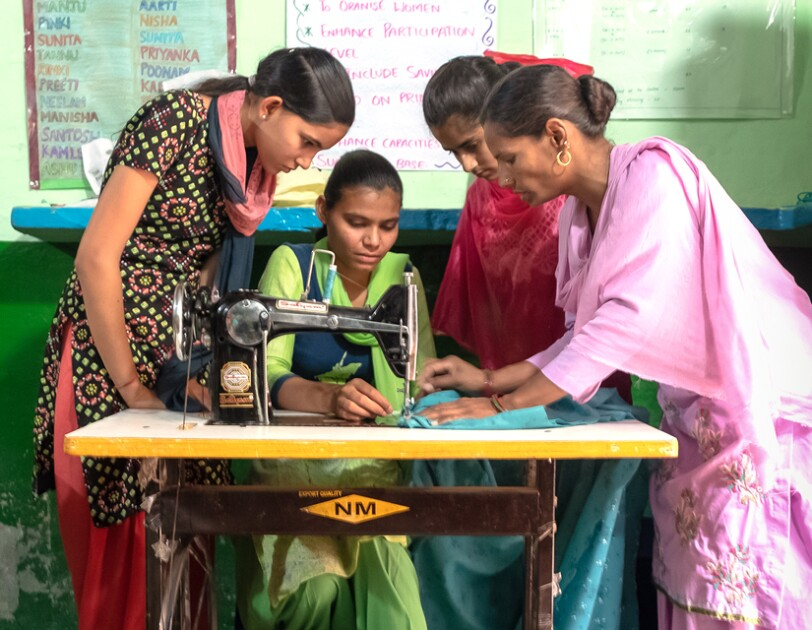 Three women stand around a woman who sits at a sewing machine.