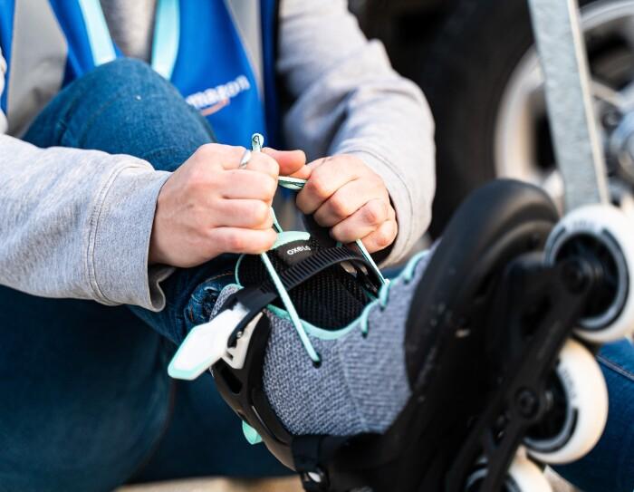 Silvia Mercado empezó el proyecto Rodes màgiques con su tía con el objetivo de salir a pasear con su prima que va en silla de ruedas. Silvia es asociada en el centro logístico de Amazon en Martorelles. Silvia se está atando los cordones de unos patines en línea. Es un primer plano de las manos y de los patines.  Va con unos jeans, un jersey gris y un chaleco de color azul.