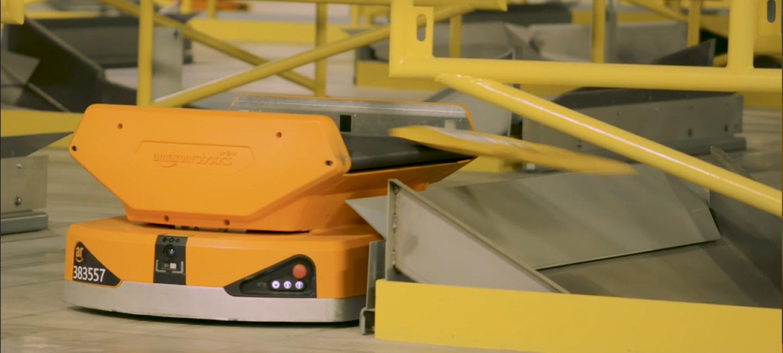 Los Pegasus Drives reciben los paquetes individualmente en su cinta transportadora, se mueven a través del campo robotizado y los colocan en la rampa. Foto lateral del drive, de color naranja, que lanza el paquete a la rampa.