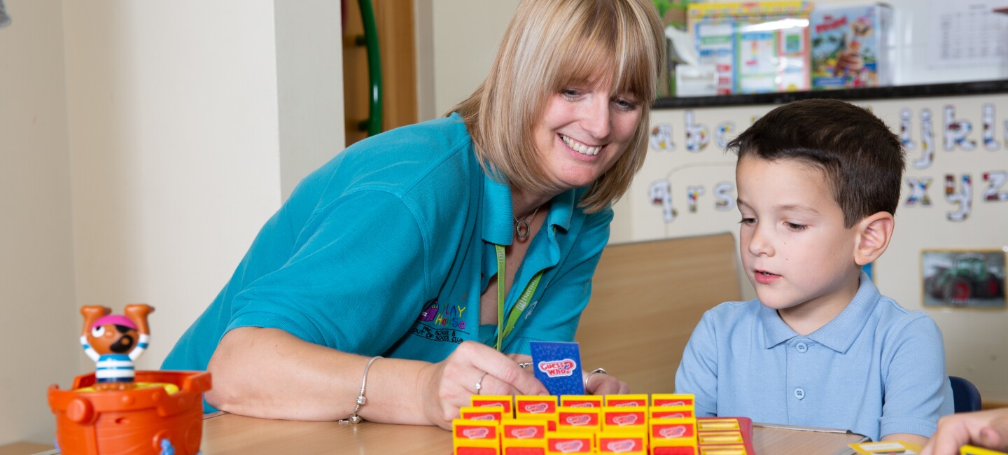 Barnardo's Service worker playing a game of Guess Who with a school child.