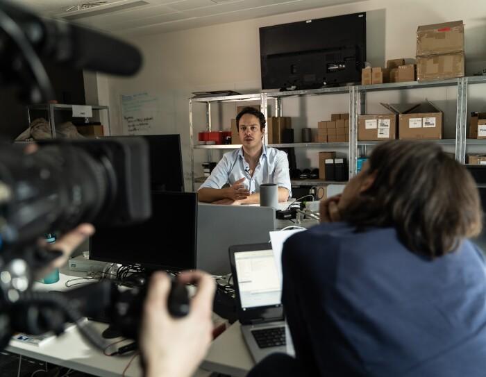 Francesco Piai, Beta Program Manager. Francesco está en su lugar de trabajo con el equipo de rodaje. Él está en el fondo, sentado en su mesa y con un dispositivo Echo. Rodeado de cajas, enfrente tiene a un cámara y a una periodista.