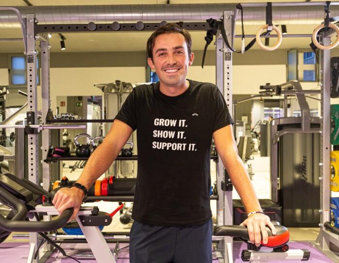 Tiago Moreira-Rato apoyado enuna bici estática. Con una camiseta negra y pantalómn azul, Tiago está apoyado a la bici, con una mano en el manillar y otra en el sillín. De fondo un gimnasio con aparatos y  pesas-