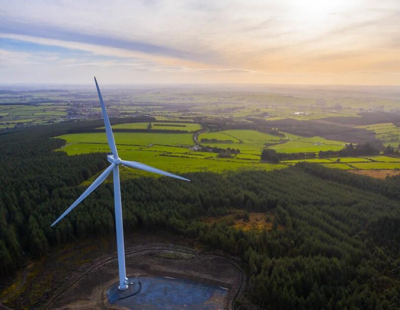 A wind turbine, from an Amazon wind farm, in front of fields in Europe.