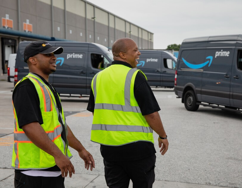 Two men in safety vests look out at vans decorated with the Amazon smile logo,